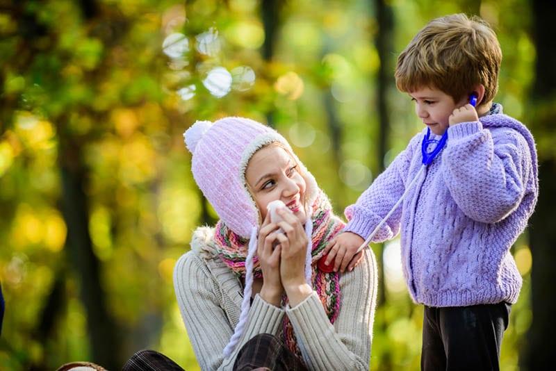 niedlichen kleinen Jungen spielen eine Rolle als Arzt mit seiner Mutter im Freien