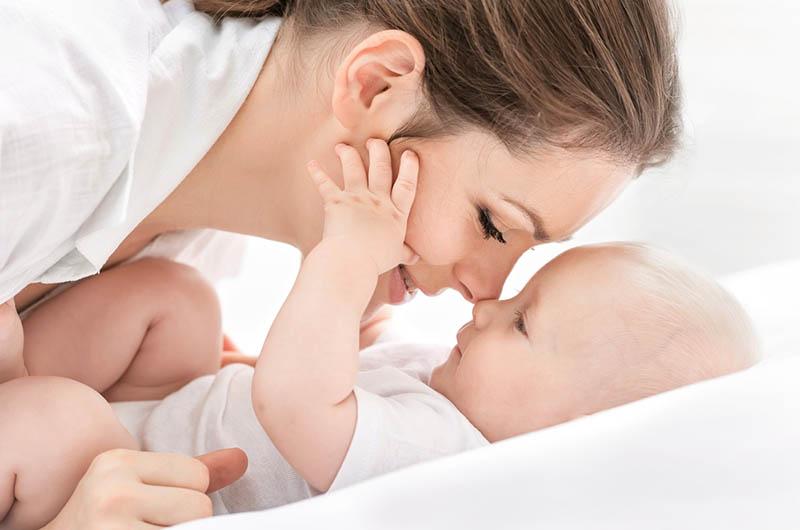 niedlichen kleinen Jungen streicheln seine glückliche Mutter auf dem Bett