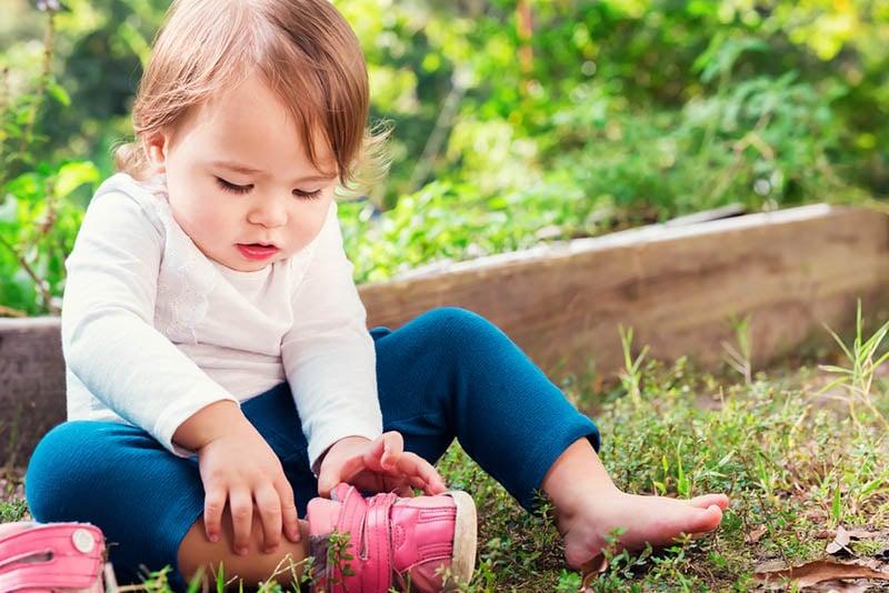 niedlichen kleinen Mädchen ausziehen ihre Schuhe im Freien auf dem Gras