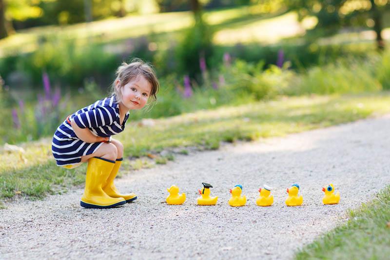 niedlichen kleinen Mädchen in gelben Stiefeln spielen mit Gummi-Enten im Freien