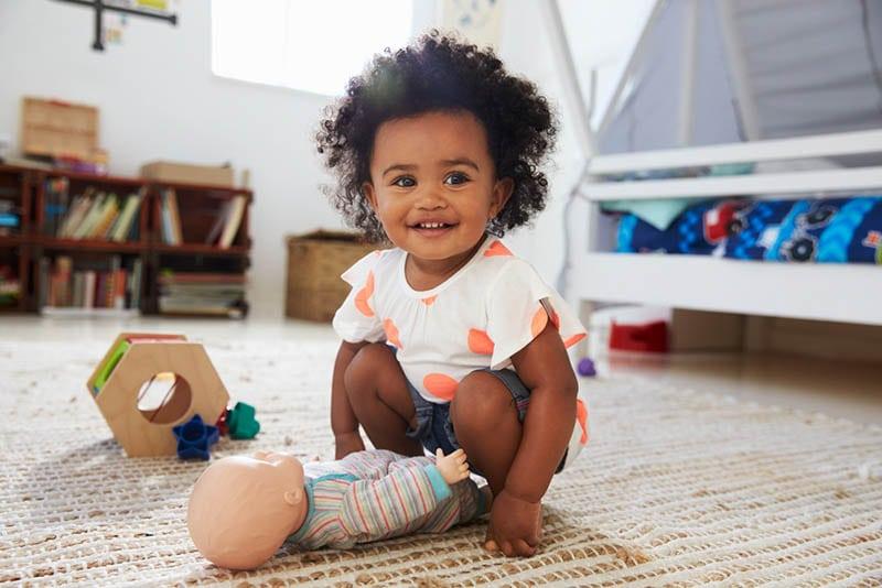 niedlichen kleinen Mädchen mit lockigem Haar spielen mit Spielzeug auf dem Boden