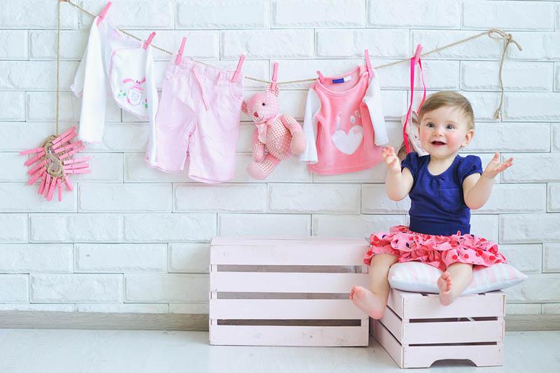 niedlichen kleinen lächelnden Mädchen mit Baby-Kleidung hängen hinter an der Wand