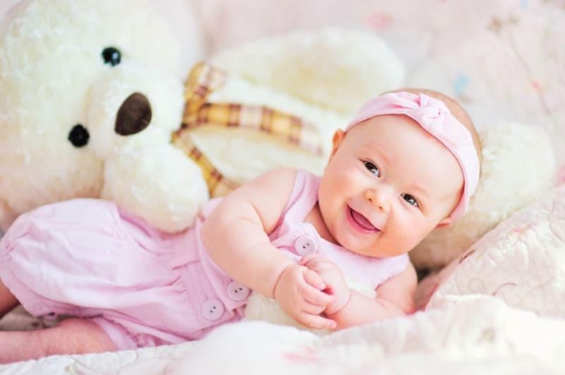 niedlichen lächelnden Baby Mädchen mit Teddybär Spielzeug auf dem Bett