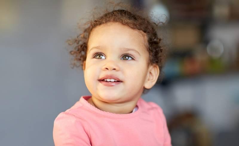 schönes kleines Mädchen lächelnd und aufblickend