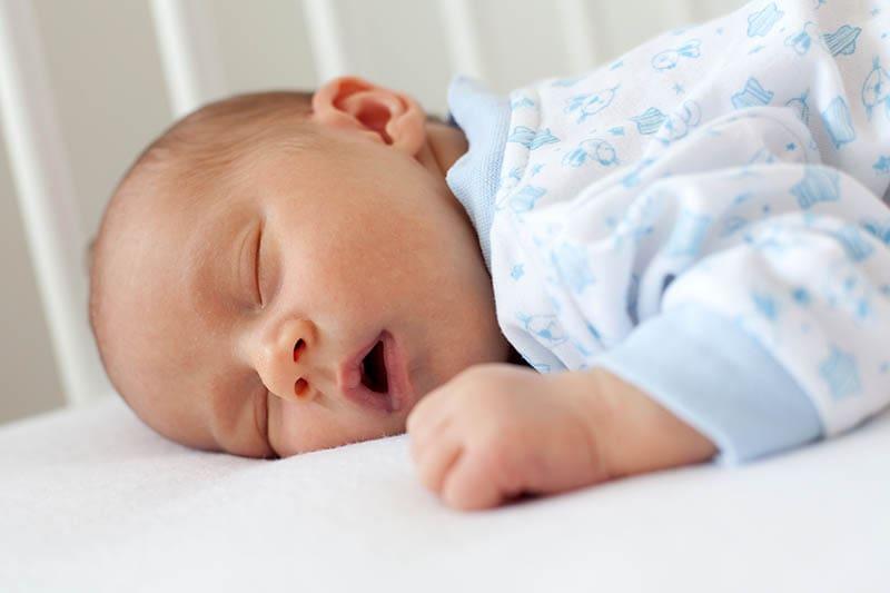 süße neugeborenes Baby schlafen auf dem Bauch in Krippe mit offenem Mund