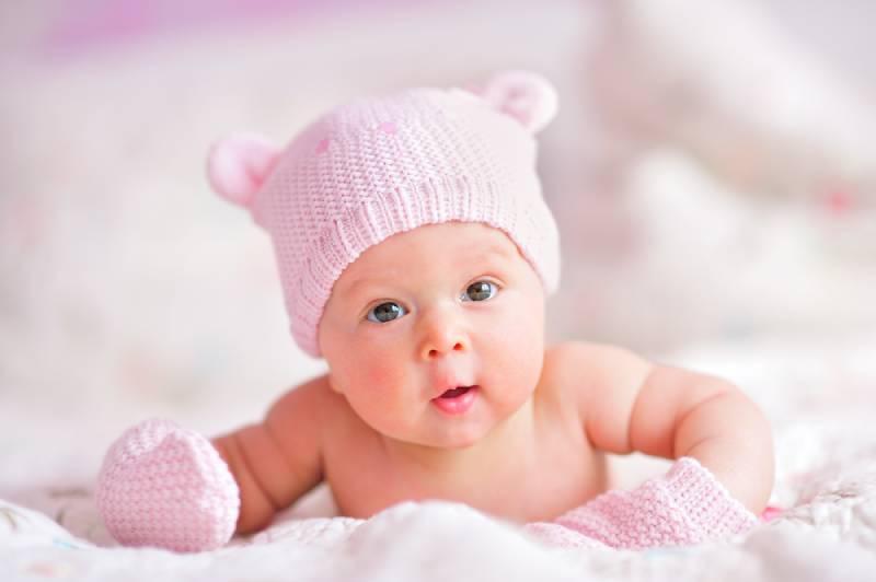 süßes Baby Mädchen mit rosa Hut auf dem Bauch liegend