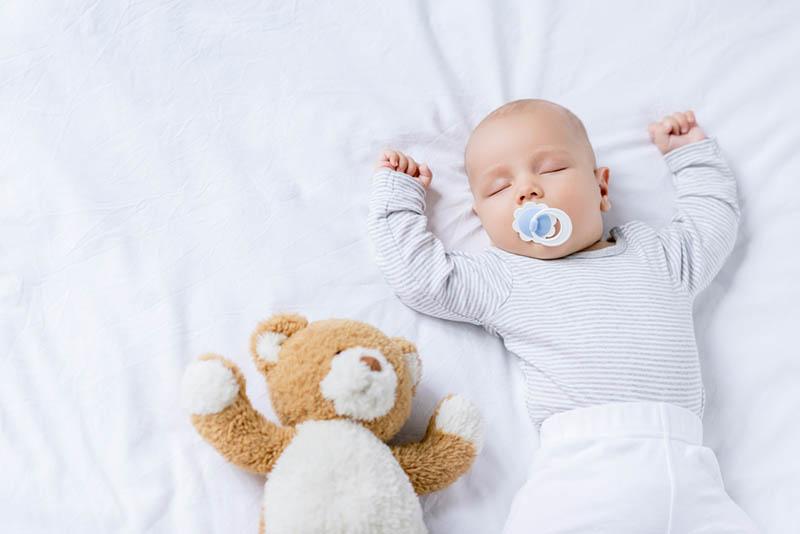 süßes Baby schläft mit Schnuller im Bett und mit Teddybär Spielzeug