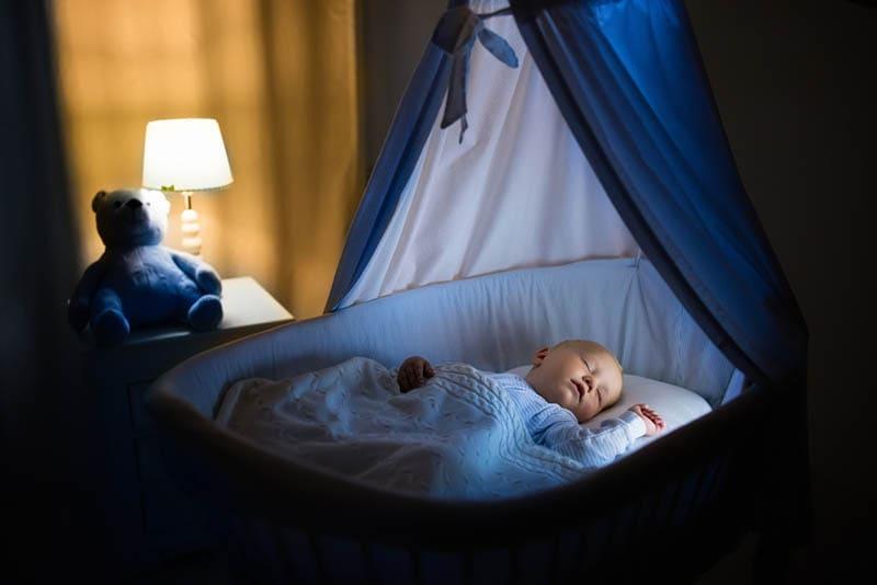 süßes Baby schläft nachts im Stubenwagen im Schlafzimmer