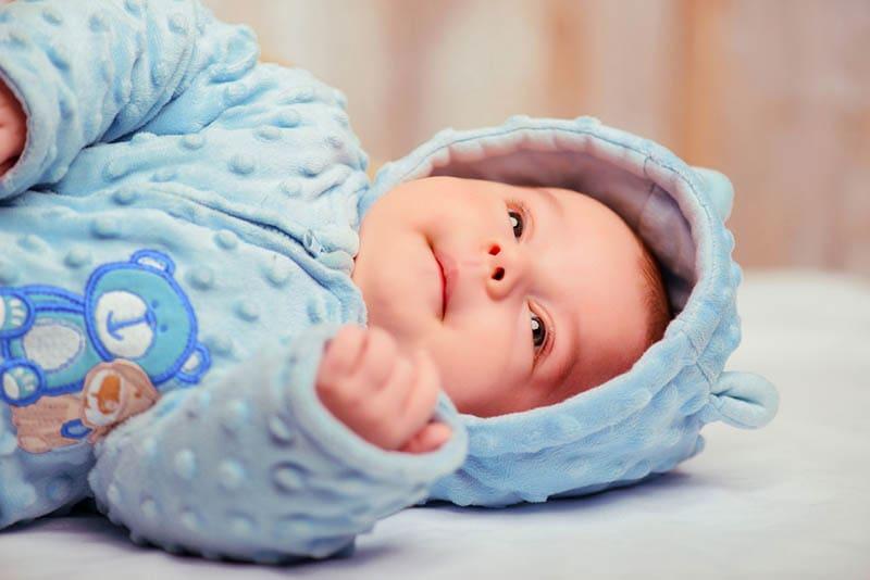 süßes Baby trägt einen blauen Körper Anzug und liegt auf dem Bett