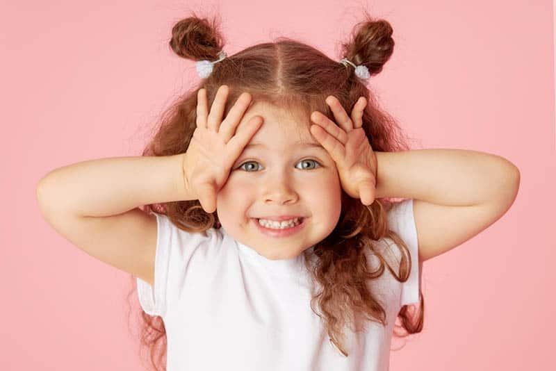 süßes kleines Mädchen hält Hände auf dem Kopf mit Gesichtsausdruck