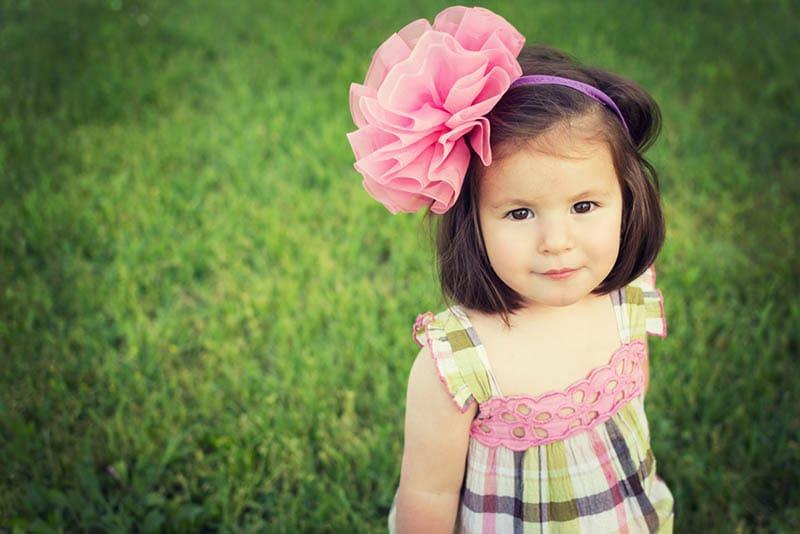 süßes kleines Mädchen mit großen rosa Stirnband im Kleid stehend auf dem Gras im Freien