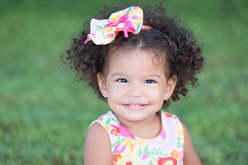 süßes kleines Mädchen trägt bunte Stirnband beim Sitzen im Freien auf dem Gras