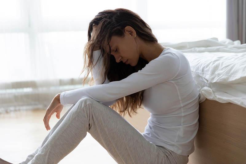 traurige junge Frau sitzt auf dem Boden im Schlafzimmer