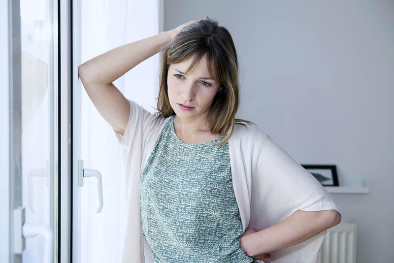 traurige junge Frau steht am Fenster zu Hause
