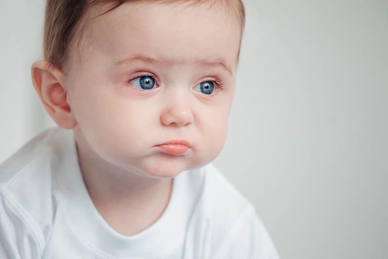 trauriges Baby mit großen blauen Augen schaut in die Ferne