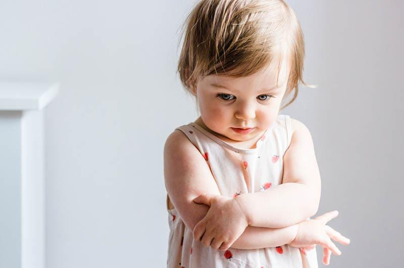 trauriges kleines Mädchen im Kleid stehend mit verschränkten Armen