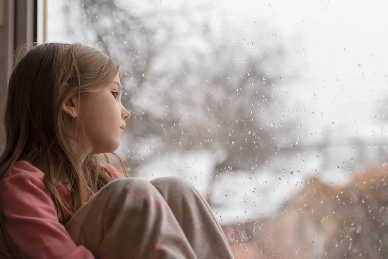 trauriges kleines Mädchen schaut durch das regnerische Fenster