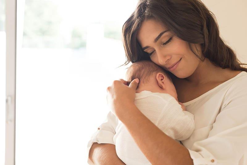 ziemlich lächelnd Mutter hält und kuscheln mit ihrem Baby auf der Brust