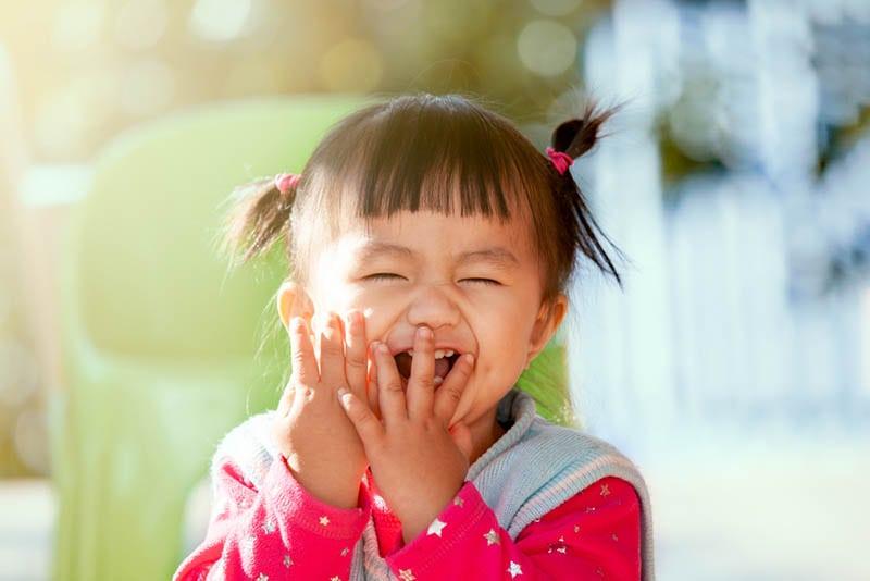 Baby-Mädchen lachen und spielen peekaboo