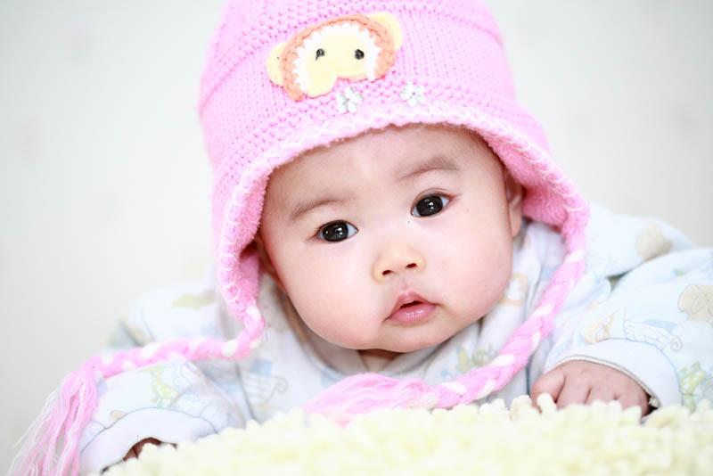 Baby Mädchen liegend auf dem Bauch mit rosa Strickmütze