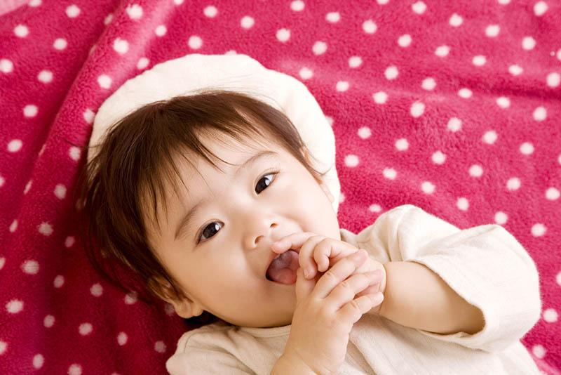 Baby Mädchen setzen Hand in den Mund, während auf dem Bett liegend