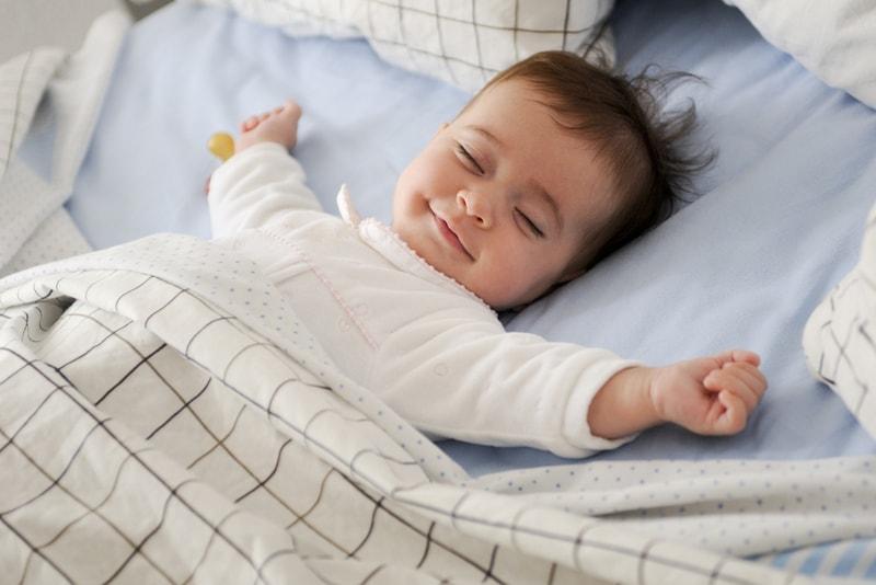 lächelndes Baby, das auf einem Bett liegt