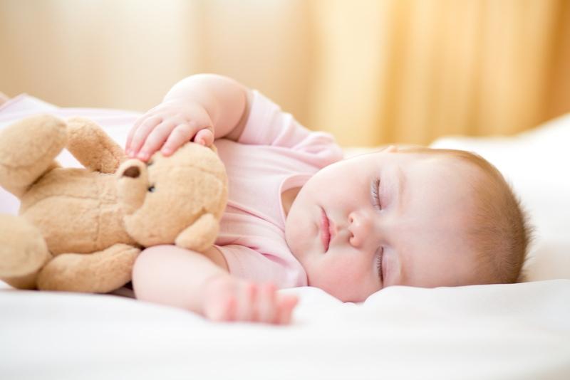 Baby, das mit Plüschtier schläft