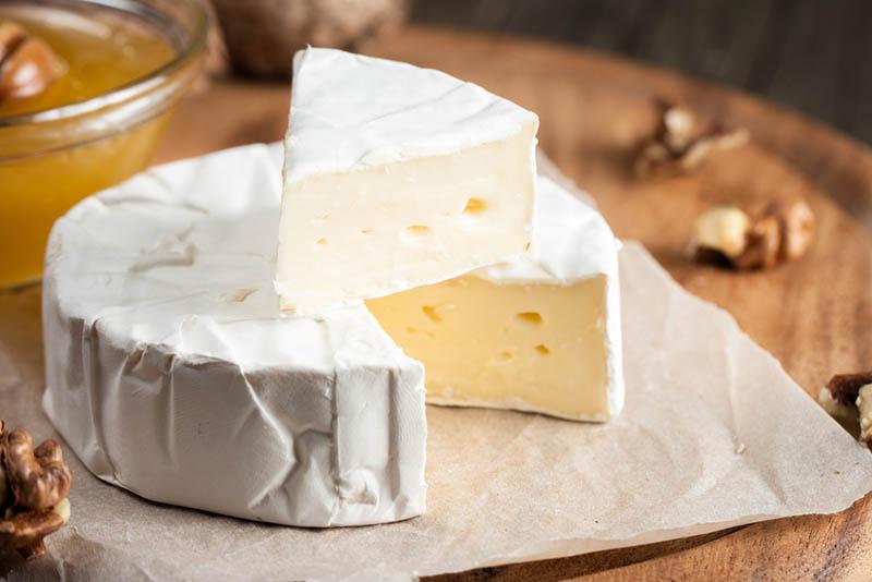 Frischer Brie-Käse und eine Scheibe auf einem Holzbrett mit Nüssen