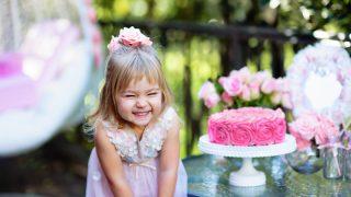 kleines Mädchen lächelt, während sie neben ihrer Geburtstagstorte steht