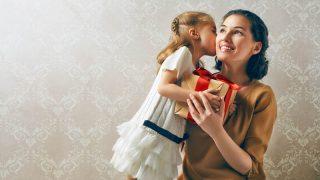 kleines Mädchen gibt ihrer Mutter einen Kuss und ein Geschenk zum Geburtstag
