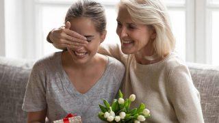 Ältere Frau überrascht ihre Schwiegertochter mit Geschenk und Blumen