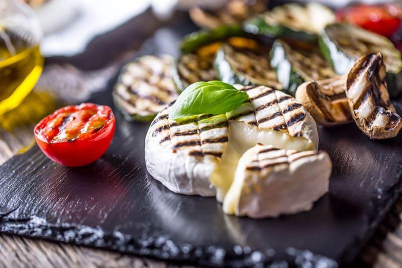 Gegrillter Camembert-Käse mit Zucchini-Tomaten, Olivenöl und Basilikumblättern