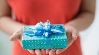 Frau im roten Kleid hält ein Geschenk