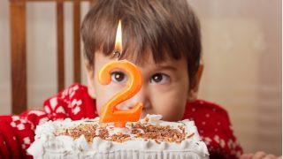 zweijähriger Junge mit seiner Geburtstagstorte