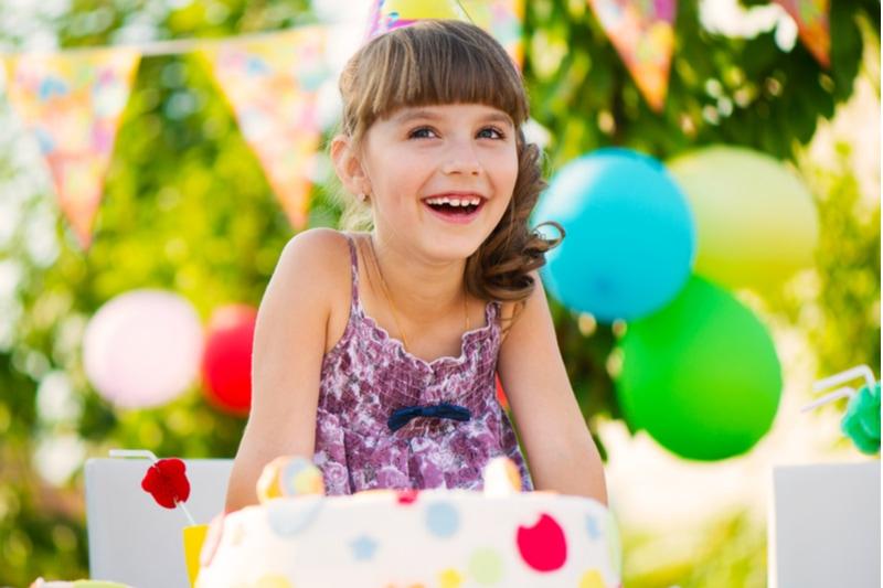 Glückliches hübsches Mädchen mit Kuchen an der Geburtstagsfeier