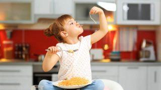 niedlichen kleinen Mädchen sitzen auf dem Tisch und essen Spaghetti