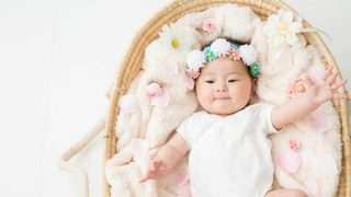 japanische Baby Mädchen liegt in einem Korb mit einer Blume Stirnband