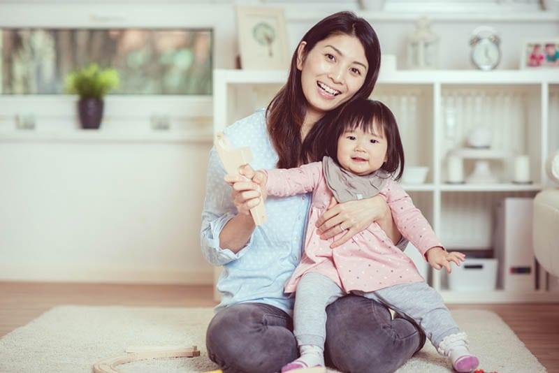Junge Mutter posiert mit kleinem Mädchen auf dem Boden