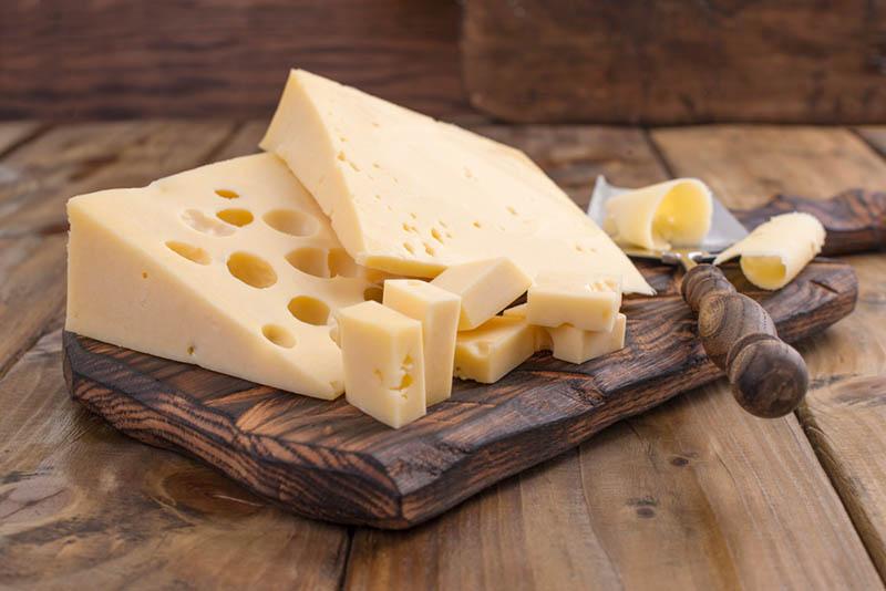 Käse mit Löchern auf dem Holzbrett mit Messer