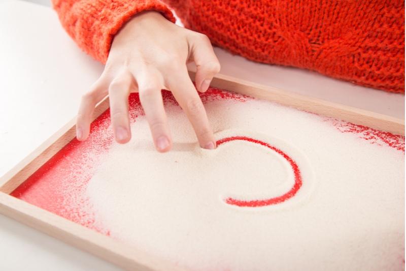 Kind, das mit montessori Sandkasten für Handtherapie spielt