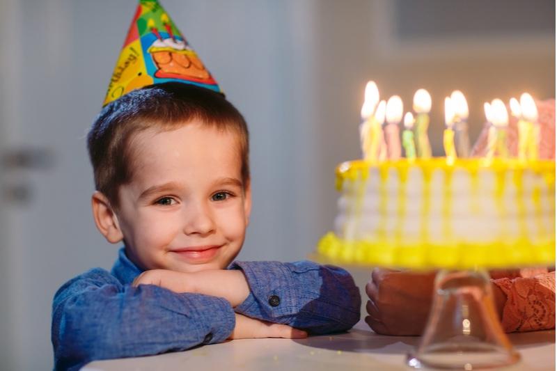 Kind nahe einer Geburtstagstorte mit Kerzen
