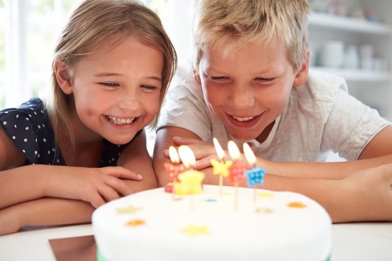 Kinder, die Geburtstag mit Kuchen feiern