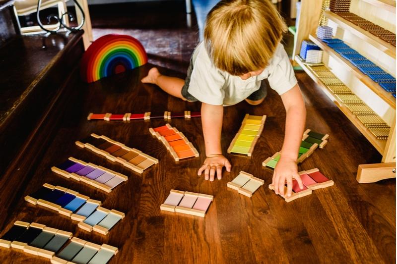 Kinder spielen und lernen mit Montessori-Farbtafeln