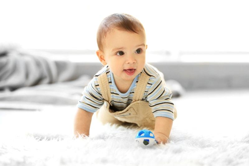Kleiner Junge mit einem Spielzeug, das zu Hause auf dem Boden kriecht