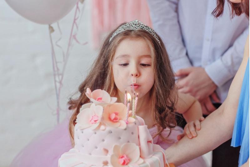 Kleines Mädchen, das Kerzen auf einer Geburtstagstorte an ihrem Geburtstag ausbläst