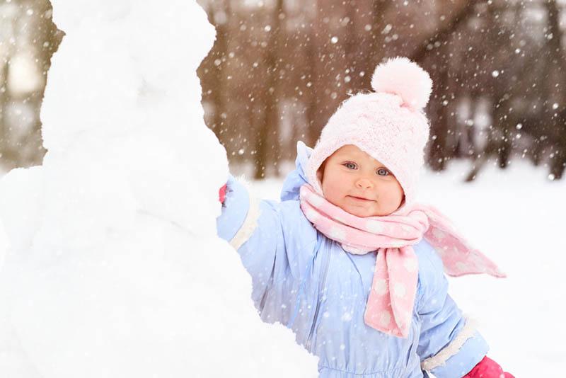 Kleines Mädchen spielt mit Schnee im Freien