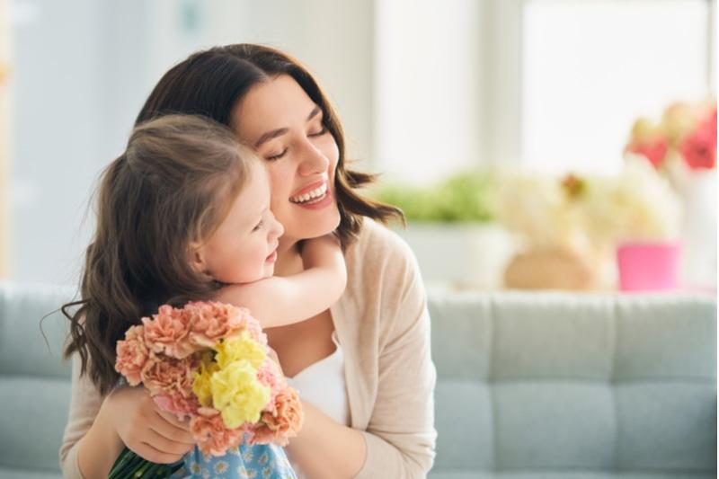 Mama und Mädchen lächeln und umarmen