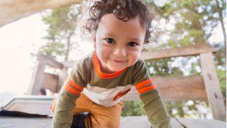 kleiner Junge mit lockigem braunem Haar krabbelt nach vorne und lächelt