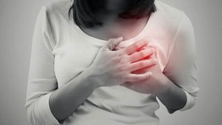 Frau hält ihre schmerzende Brust aufgrund von Milchbläschen fest