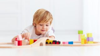 süßes Kind, das mit Spielzeugbahnstraße zu Hause spielt
